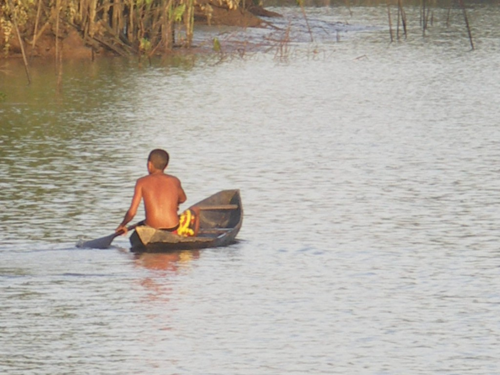 A young local native to the island of Marajó rows his canoe up the river.
