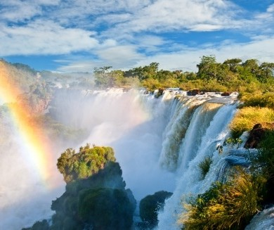 A rainbow forms over the falls of Iguacu.