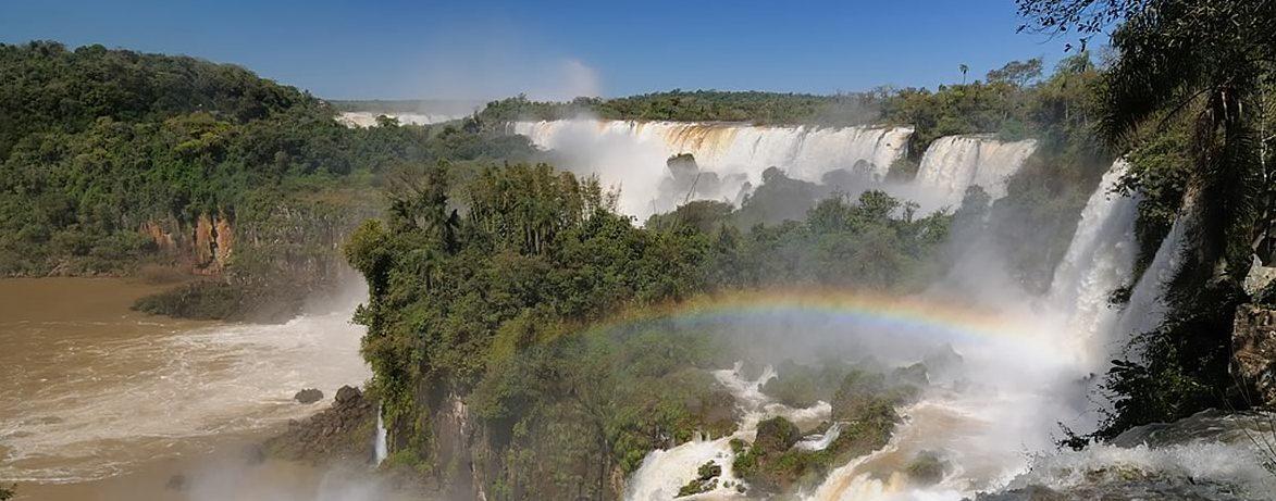 A rainbow forms over the Iguassu falls.