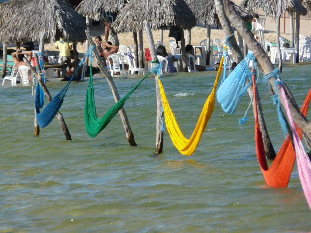 Multi-coloured hammocks suspended above the warm water.