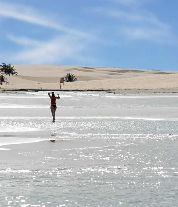 A woman enjoys walking accross a shimmering lagoon in Jericoacoara.
