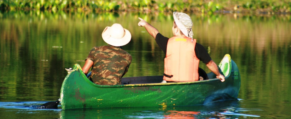An excited bird watcher points from his canoe in Pantanal.