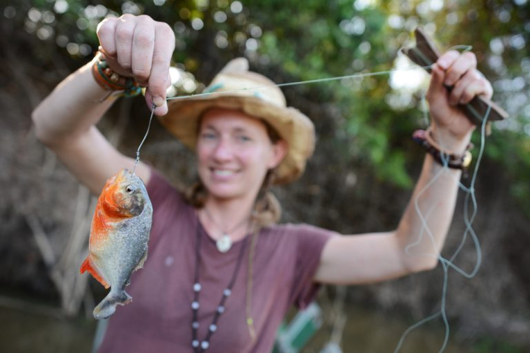 A tourist shows off her catch in the Amazon.