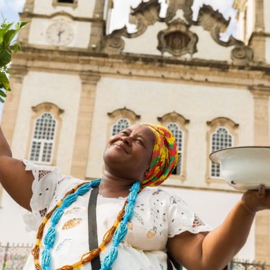 A woman dressed in traditional clothes from Bahia, holding ingredients to cook.