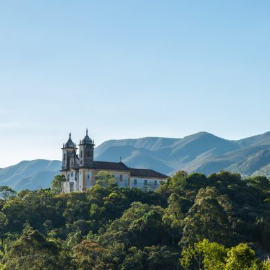 A shot of Ouro Preto church from afar, forest covers the lower part of the photo.