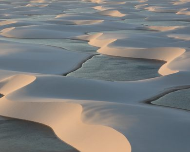 The sunset bounces off the rainwater lagoons in the Lençóis Maranhenses.