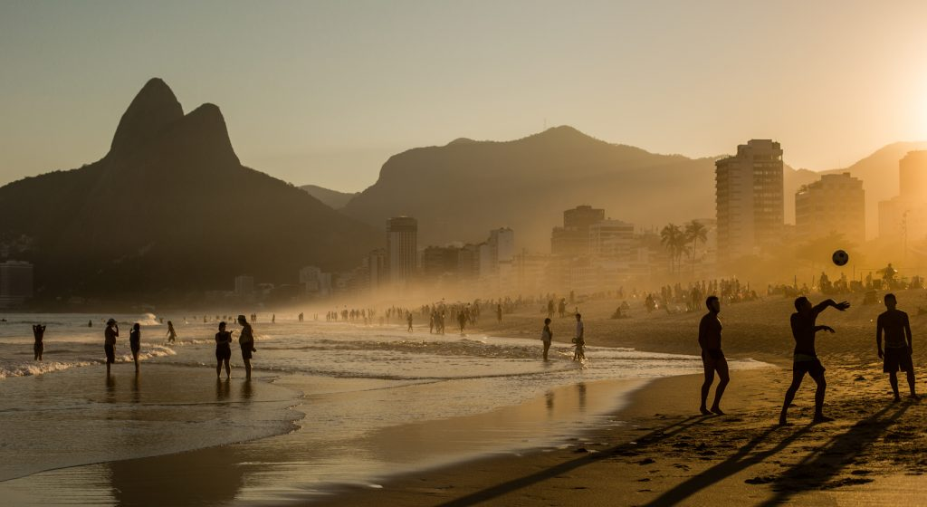 Sunset at Copacabana beach, silhouettes playing football on the sand.