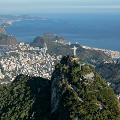 Aerial view of Corcovado from above and behind showing the entire bay of Rio de Janeiro in the background.