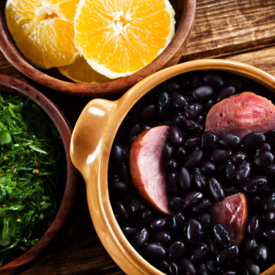Feijoada with a dish of orange slices and kale.
