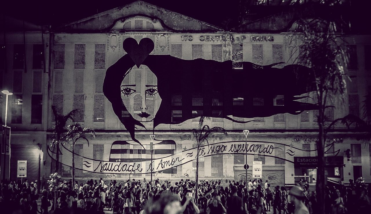 Black and white photo of crowd watching a projection on a wall in Brazil.