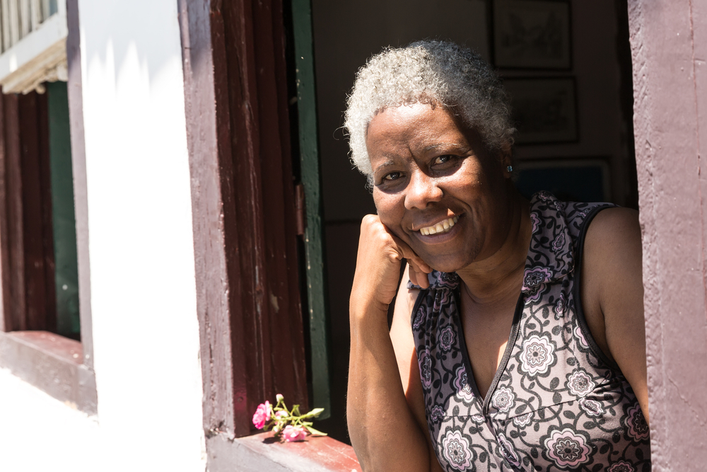 Woman smiles from her open window in Minas Gerais.